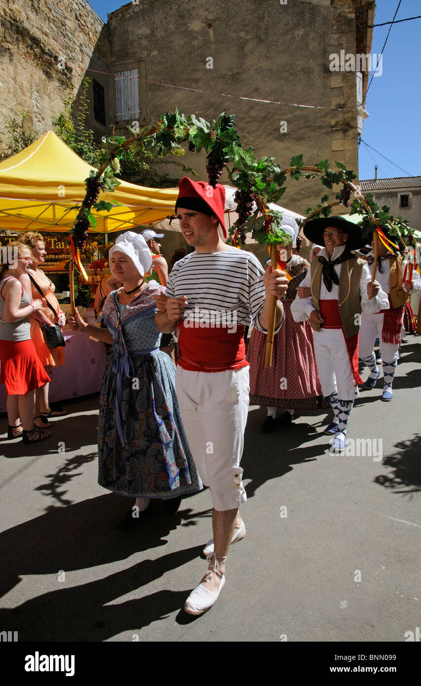 Men & women wearing traditional costumes parade to mark the opening of the Olive Festival in the French town - Stock Image