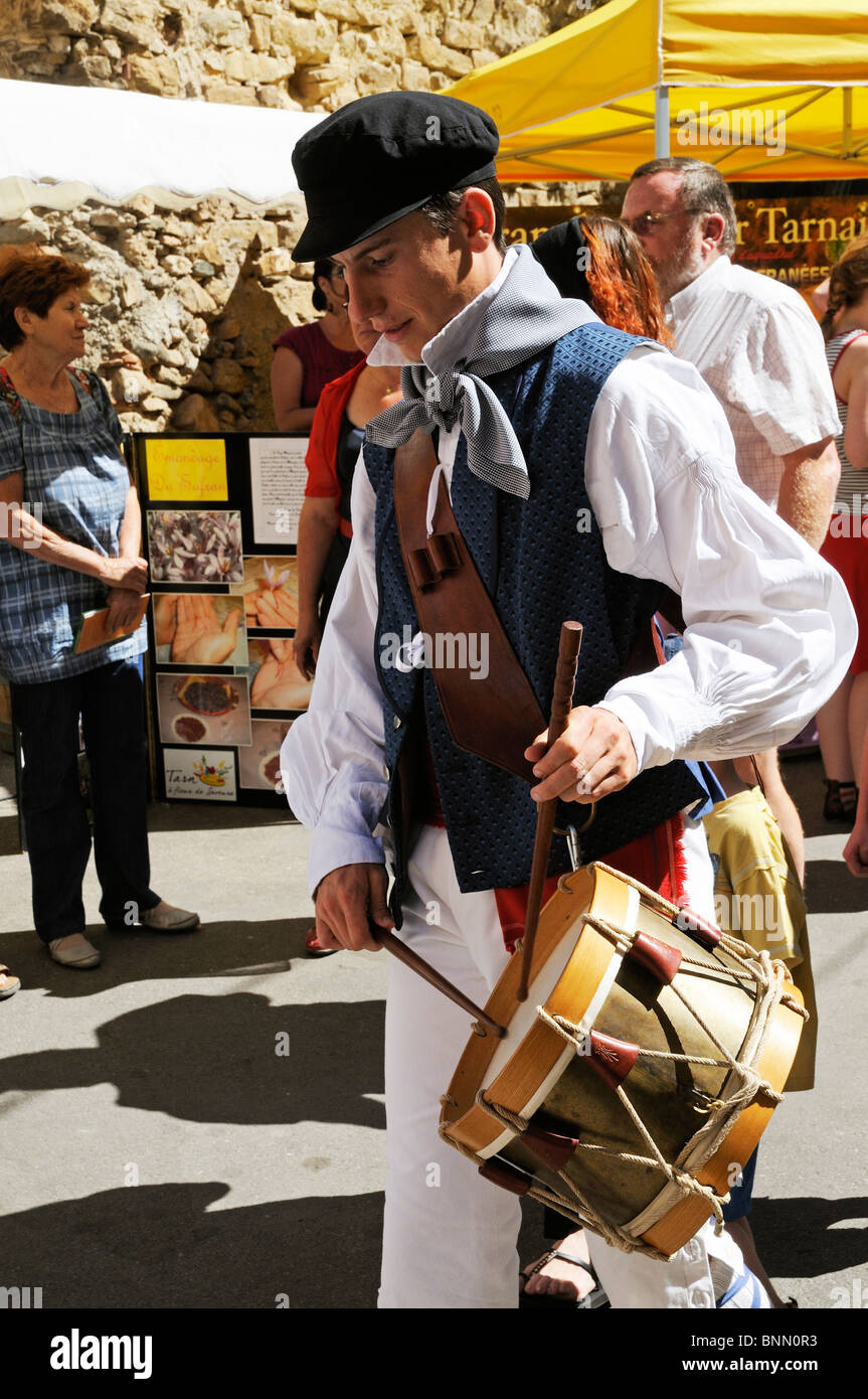 Man playing a drum & wearing traditional costume parade to mark the opening of the Olive Festival of Bize Minervois - Stock Image
