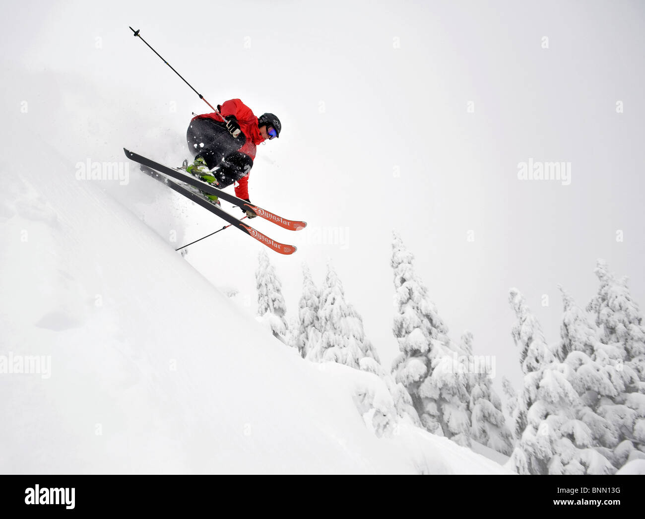 A skier gets a little air while skiing downhill at the Eaglecrest Ski area in Juneau, Alaska - Stock Image