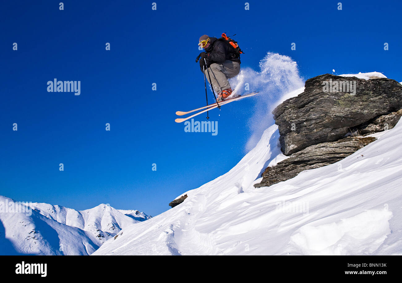 A skier jumps off a rock in Hatcher Pass and skiis downhill, Alaska - Stock Image