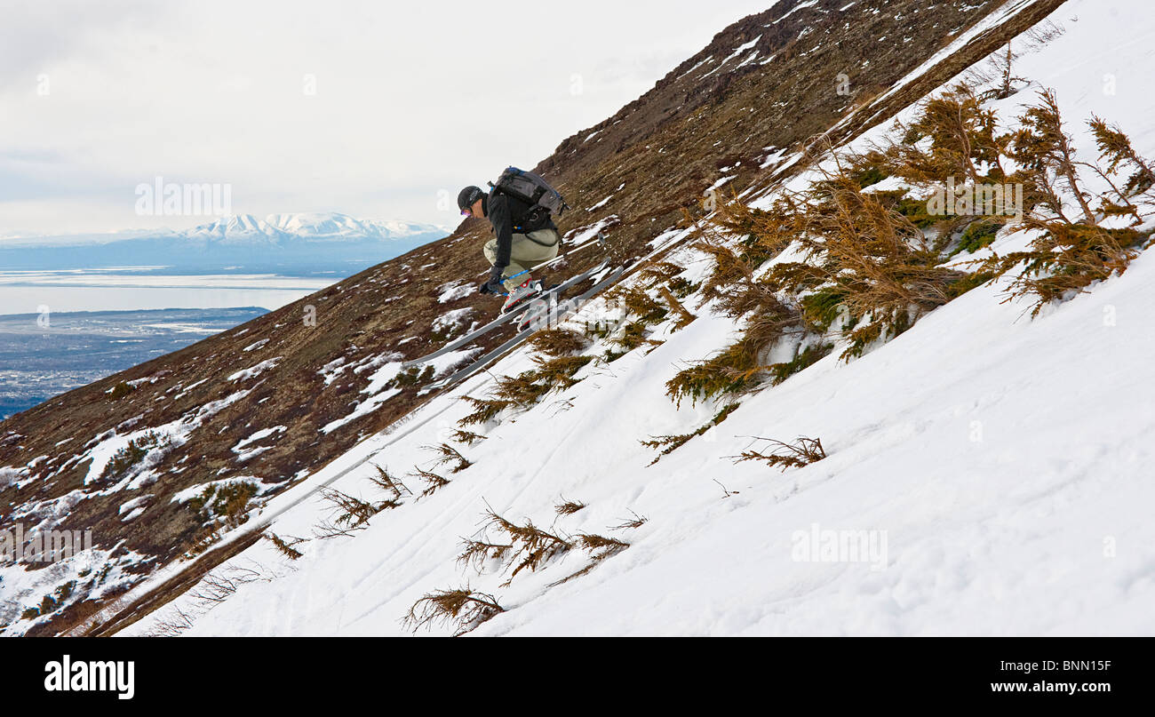 A backcountry skier catches a small air while skiing between shrubs on the side of Peak 3 near Anchorage, Alaska - Stock Image
