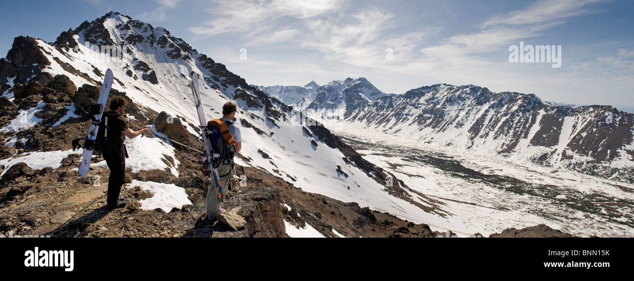 A backcountry snowboarder and skier enjoy the view from the west ridgeline of Powerline Pass near Anchorage, Alaska - Stock Image
