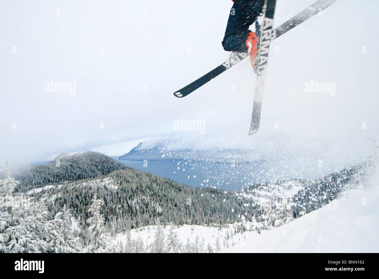 Backcountry skier jumps into deep powder, Wrangell Island, Tongass National Forest, Alaska - Stock Image