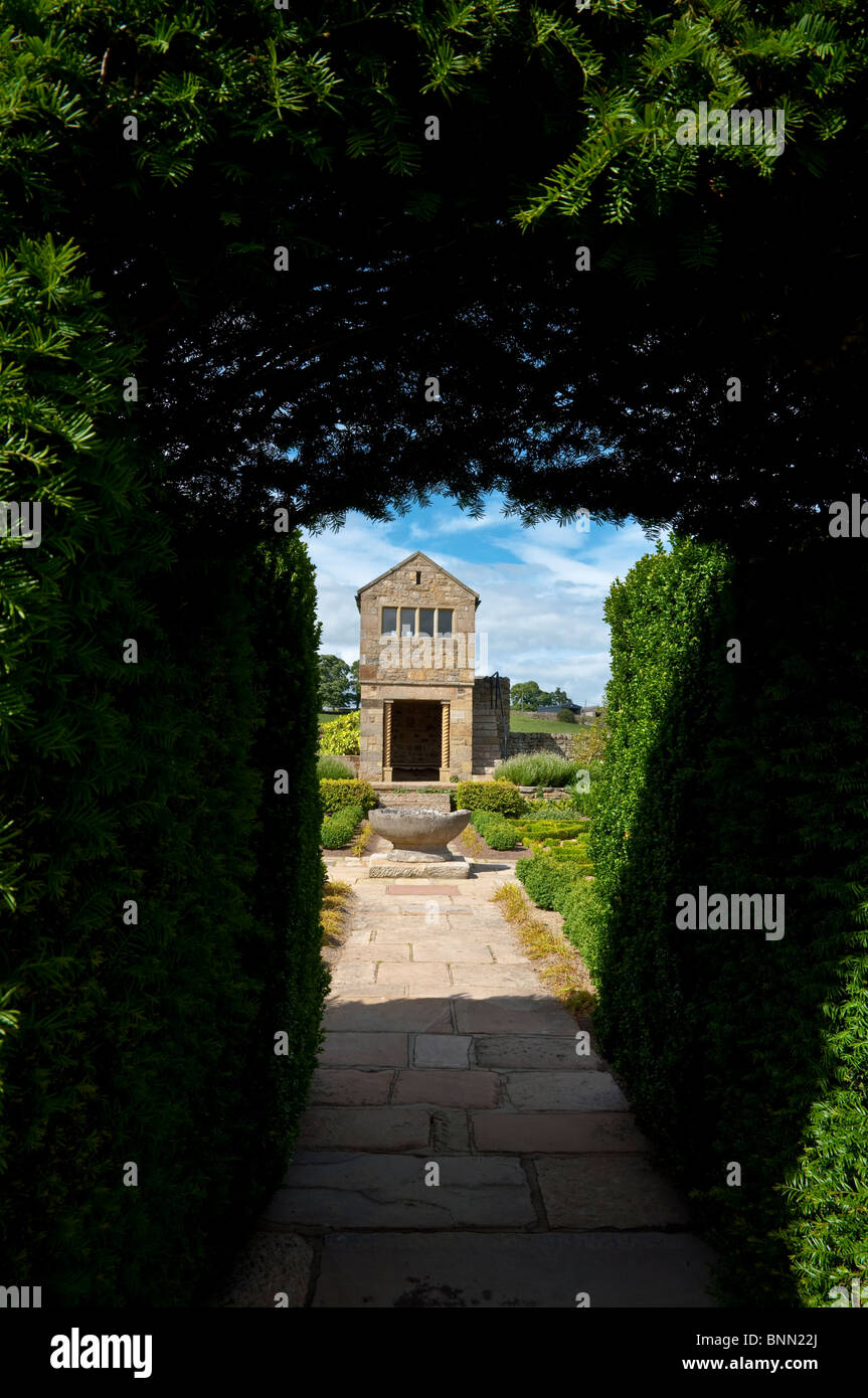 Herterton House Garden, Nr Cambo, Northumberland, UK - The Parterre / Fancy Garden - viewed though a Yew hedge archway - Stock Image