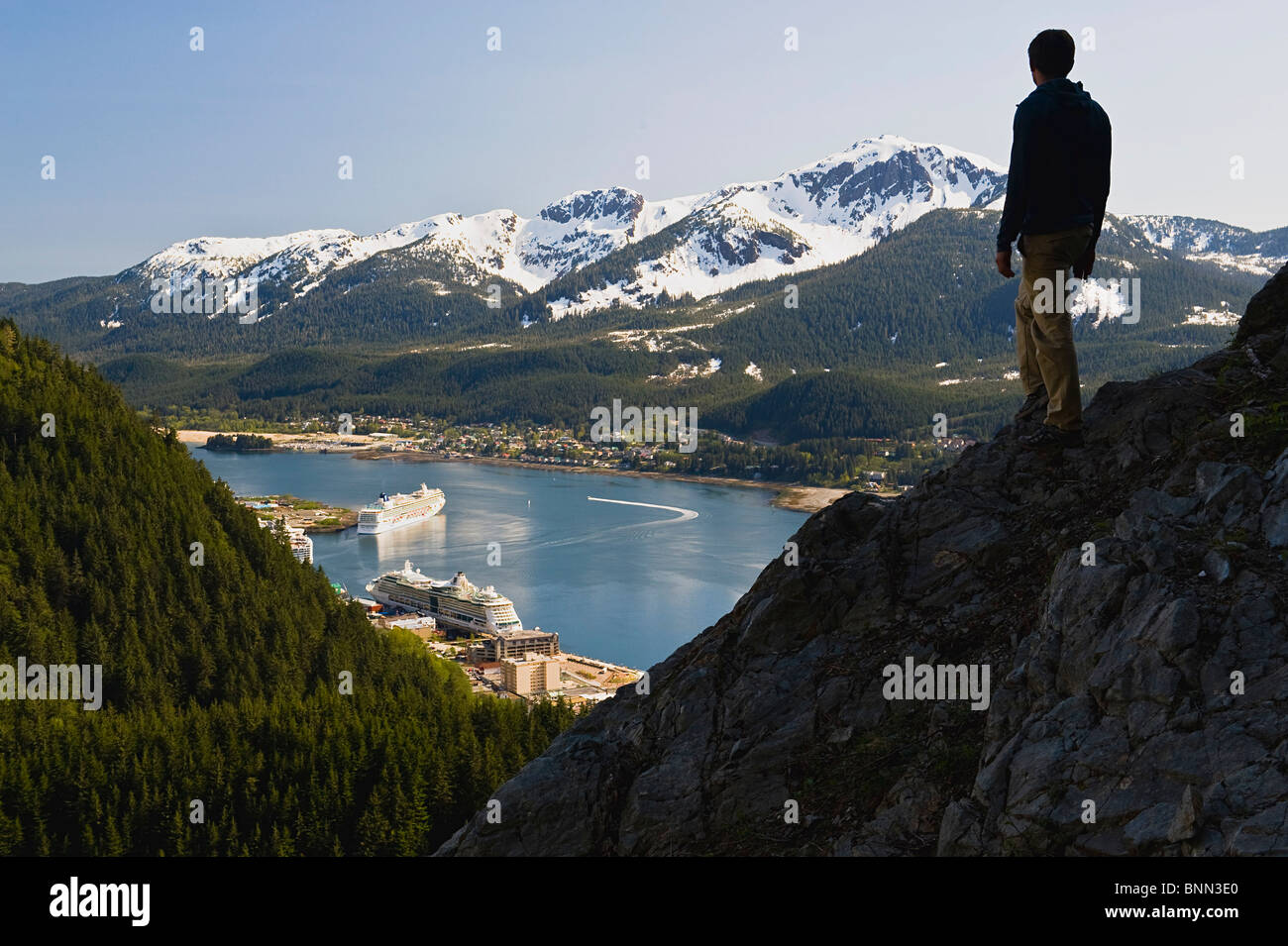 A hiker takes in the view of Gastineau Channel, Mt. Jumbo, and Downtown Juneau from the side of Mt. Roberts in Alaska, - Stock Image