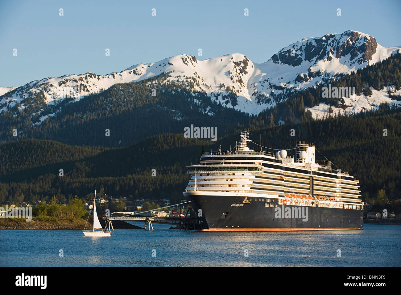 A sailboat passes in front of the docked Holland America Line cruise ship/n'Zuiderdam' in Gastineau Channel, - Stock Image