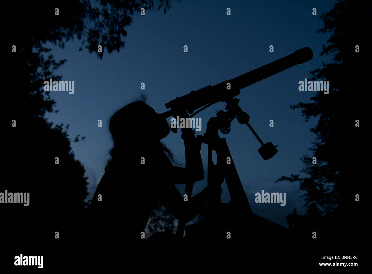 girl looking through telescope - Stock Image