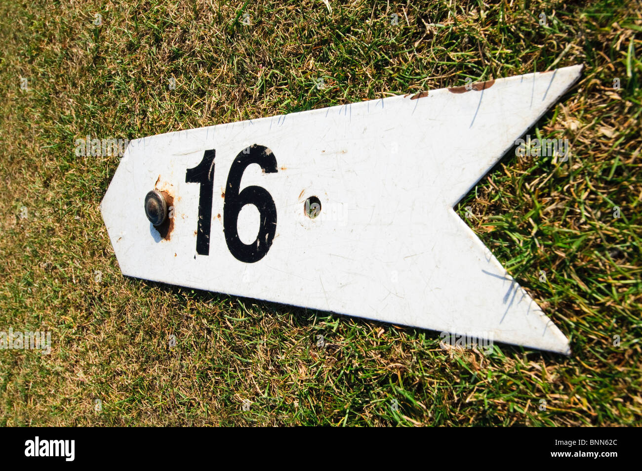 An arrow marking the 16th hole on a pitch and putt course - Stock Image