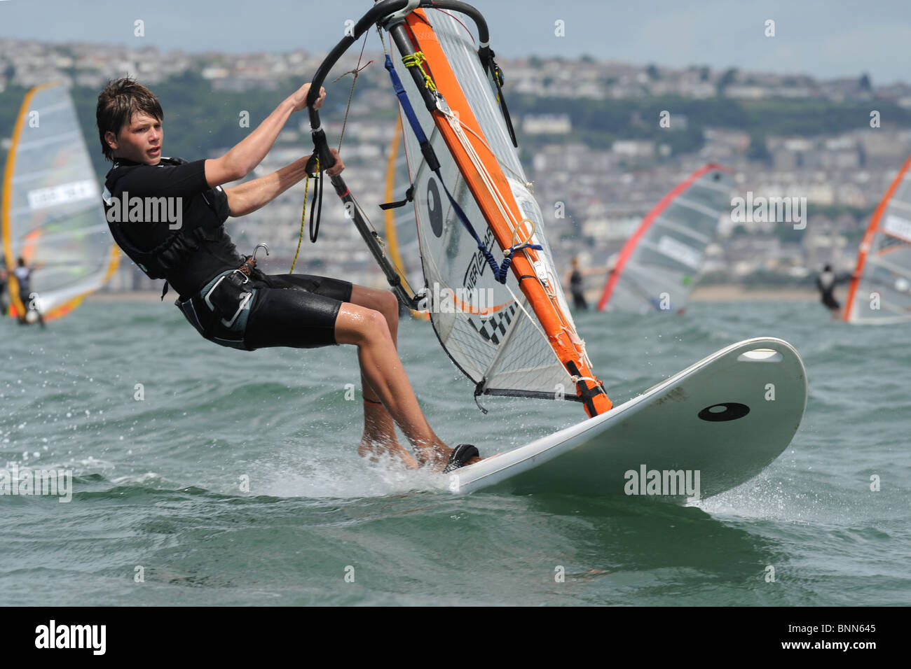 youth windsurfer  heads upwind with hands gripping boom and board flying over the waves, Swansea Bay site of Tidal Stock Photo