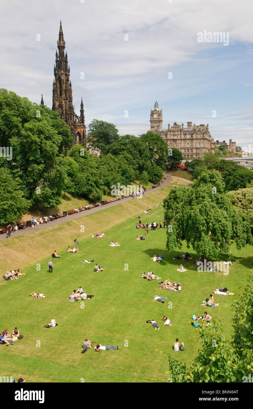 People enjoying the sun in Prince's Street Gardens, Edinburgh, with the Scott Monument in the background. - Stock Image
