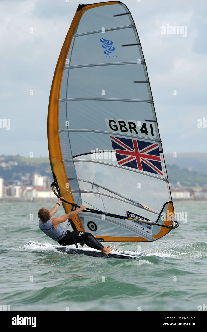 Alli Masters heads up wind with feet on rail of board . A union jack flag adorns his yellow and white sail. Swansea - Stock Image