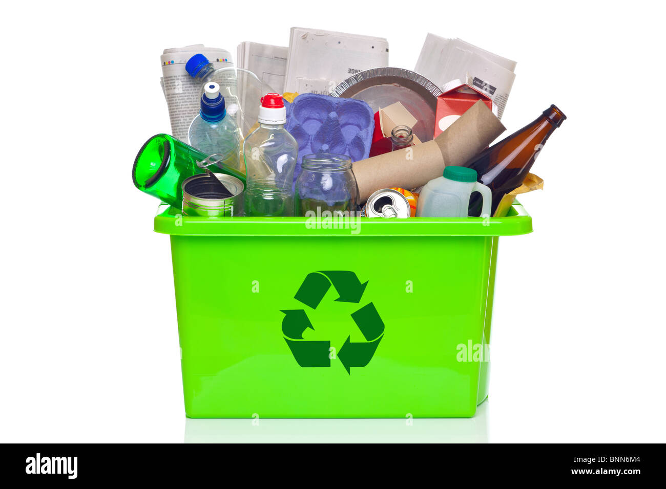 Photo of a green recycling bin full of recyclable items isolated on a white background. - Stock Image