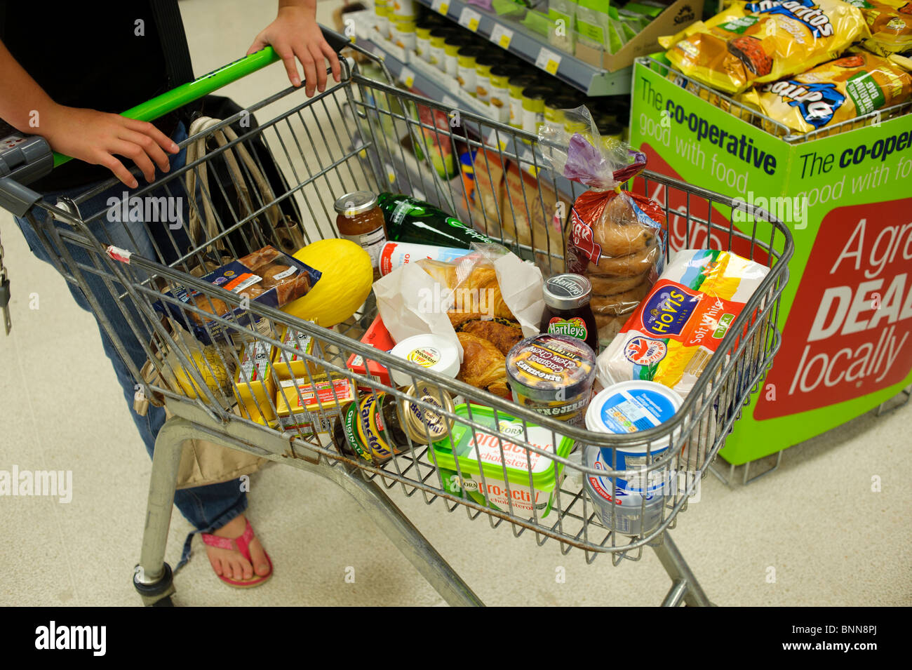 A woman pushing a Small shopping trolley with various items of fresh food Co-Op supermarket, UK - Stock Image