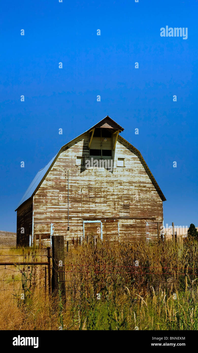 Old barn with barb wire fence in front under blue sky - Stock Image
