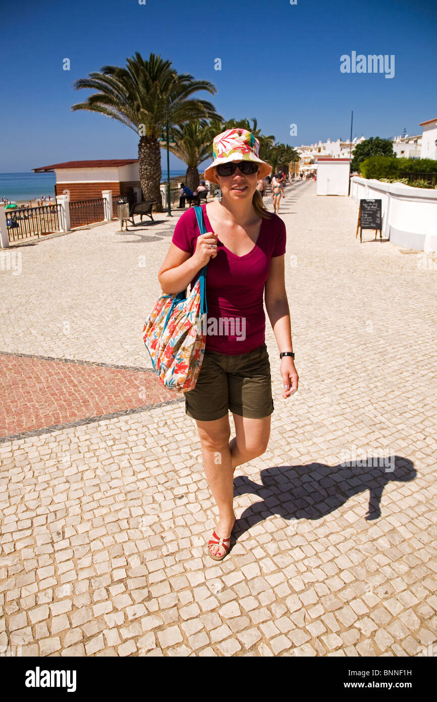 A female holidaymaker walks along the promenade at Luz in Lagos on the Algarve coast of Portugal. - Stock Image