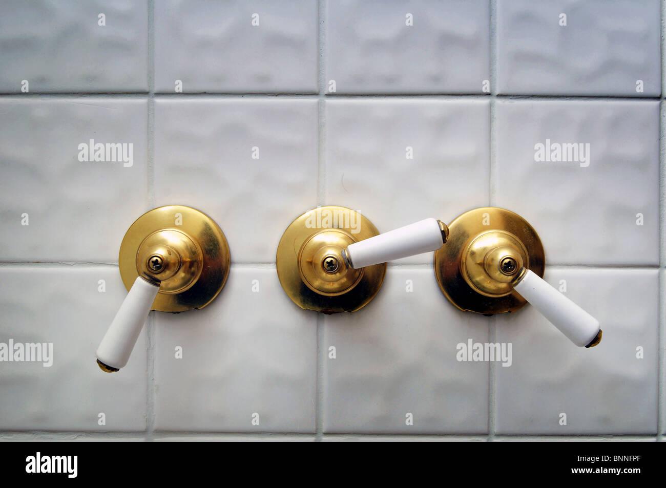Three golden shower valve handles ona big white empty tile shower ...