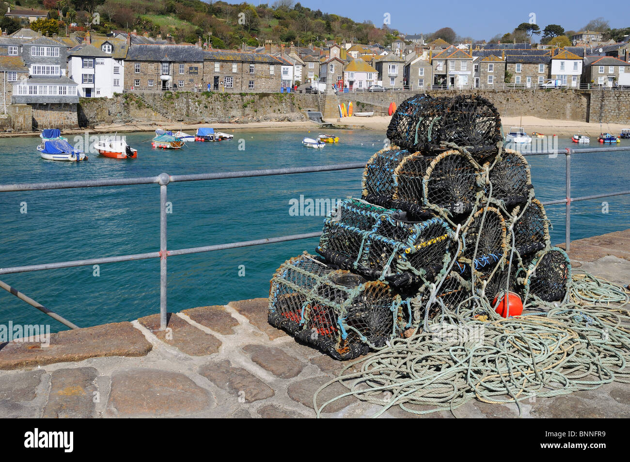 crab and lobster pots harbourside at mousehole in cornwall, uk - Stock Image