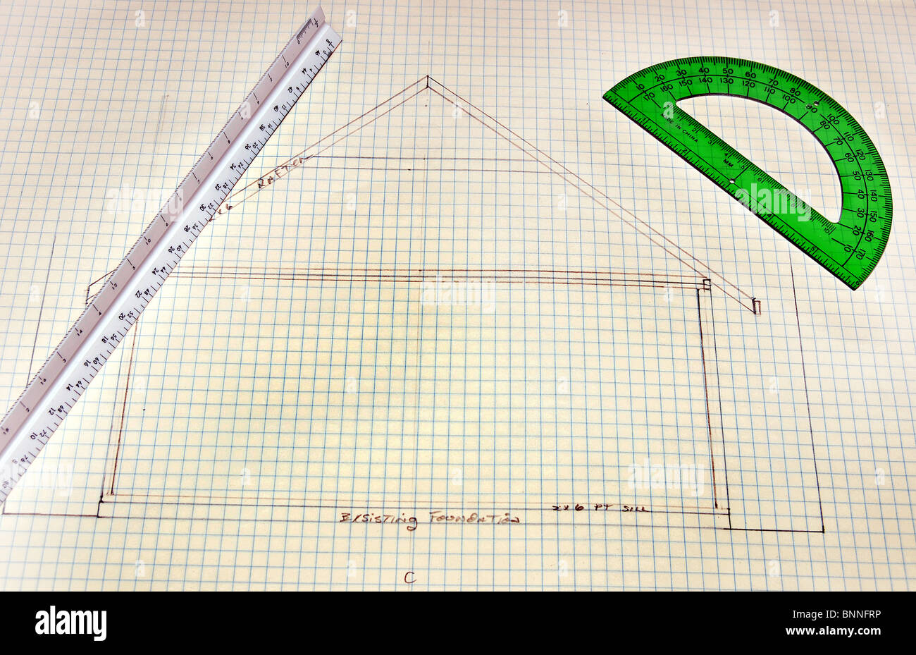 rough sketch of house floor plans on grid paper with green ruler