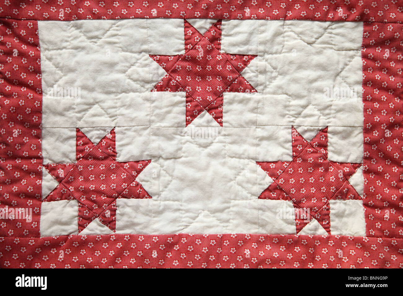 three eight-point quilted stars with a border - Stock Image