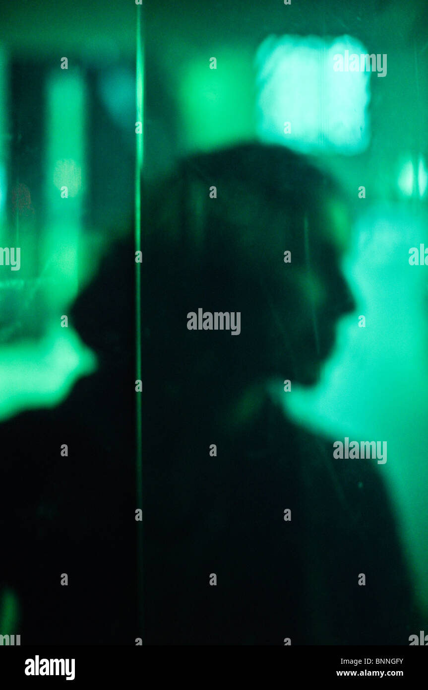 Silhouette in green of a young woman behind plastic sheeting. - Stock Image