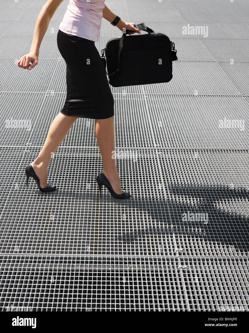 side view of business woman balancing on high heels. Copy space - Stock Image