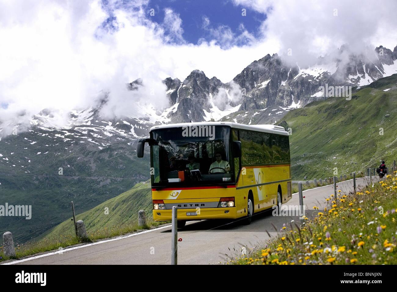 Switzerland swiss traffic bus Furka Pass postal car canton Uri mountain pass flowers flower meadow mountains clouds - Stock Image