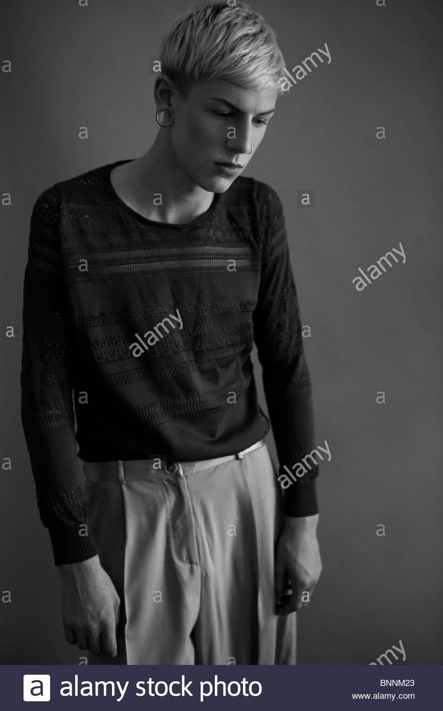 punk boy with piercings that is slumped slightly similar to an elderly man suggests an illness or unhappiness - Stock Image