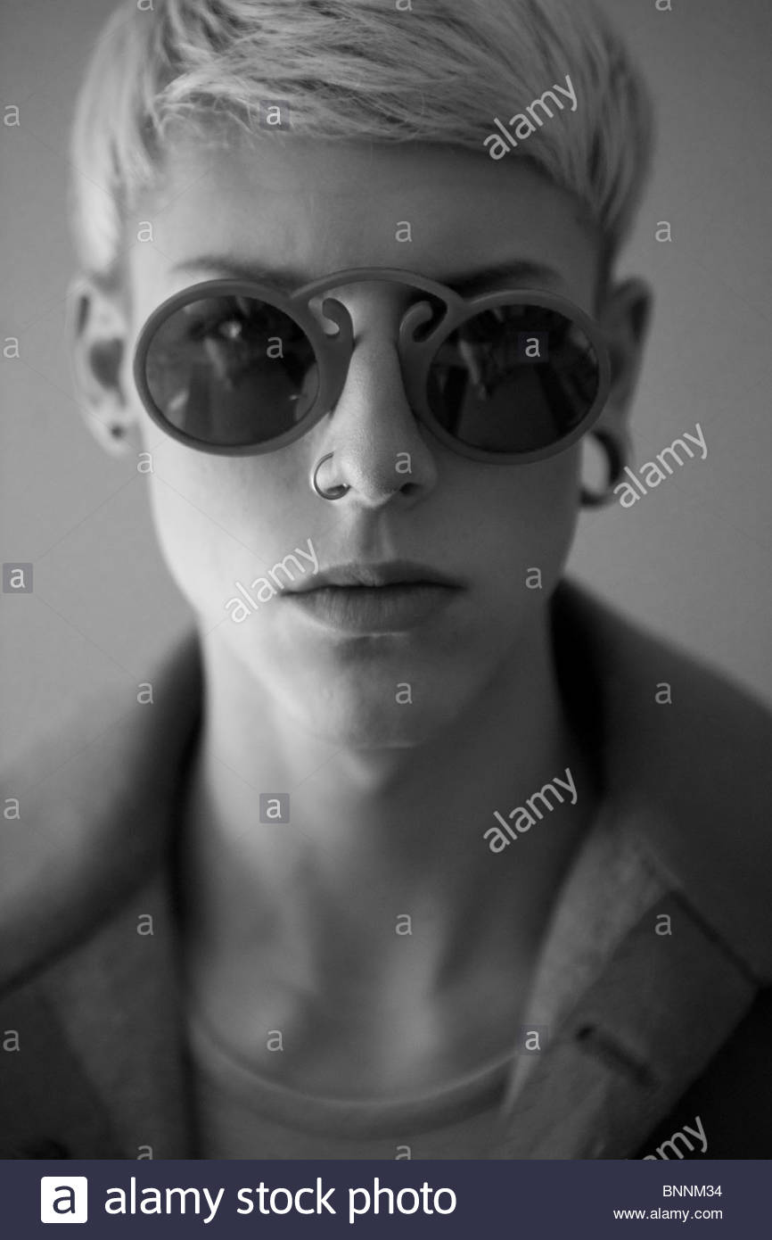 Young blonde boy looking at the camera. He is wearing a round glasses with a nose and ear piercing. Stock Photo