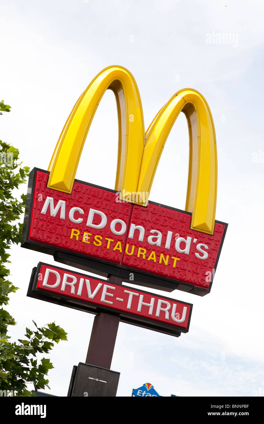 McDonald's sign and company logo on post with drive-thru sign at West Quay, Southampton. - Stock Image