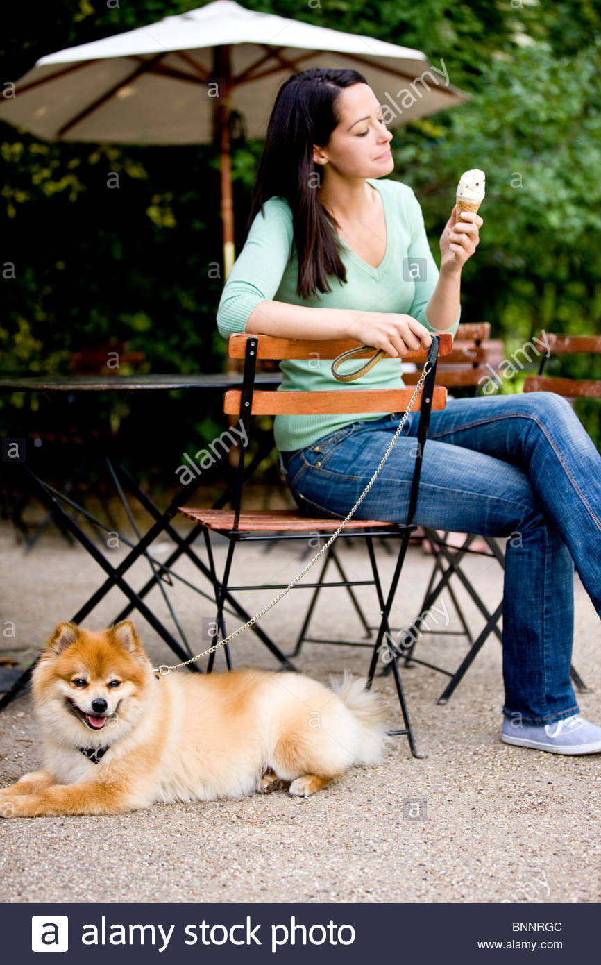A young woman with her dog at a cafe, eating an ice cream - Stock Image