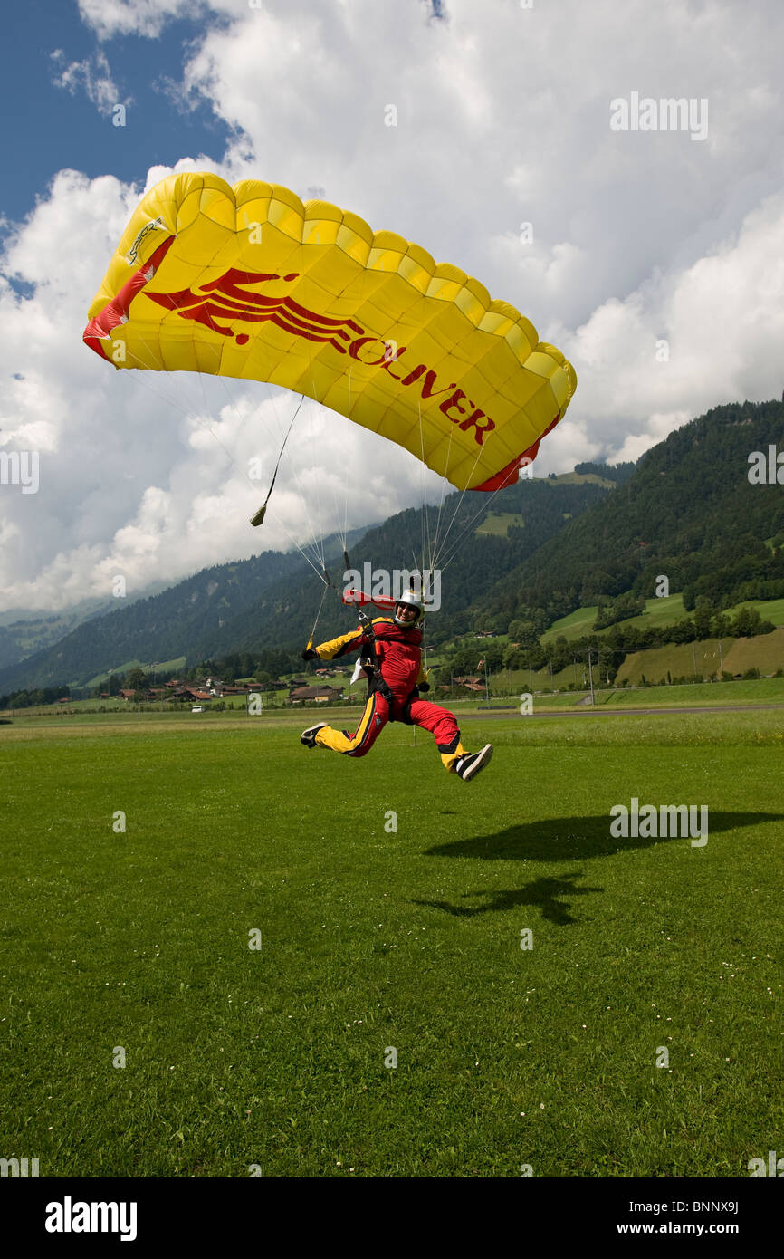 Skydiver camera flayer is landing his parachute safely. He is touch down on the shadow of his canopy. - Stock Image