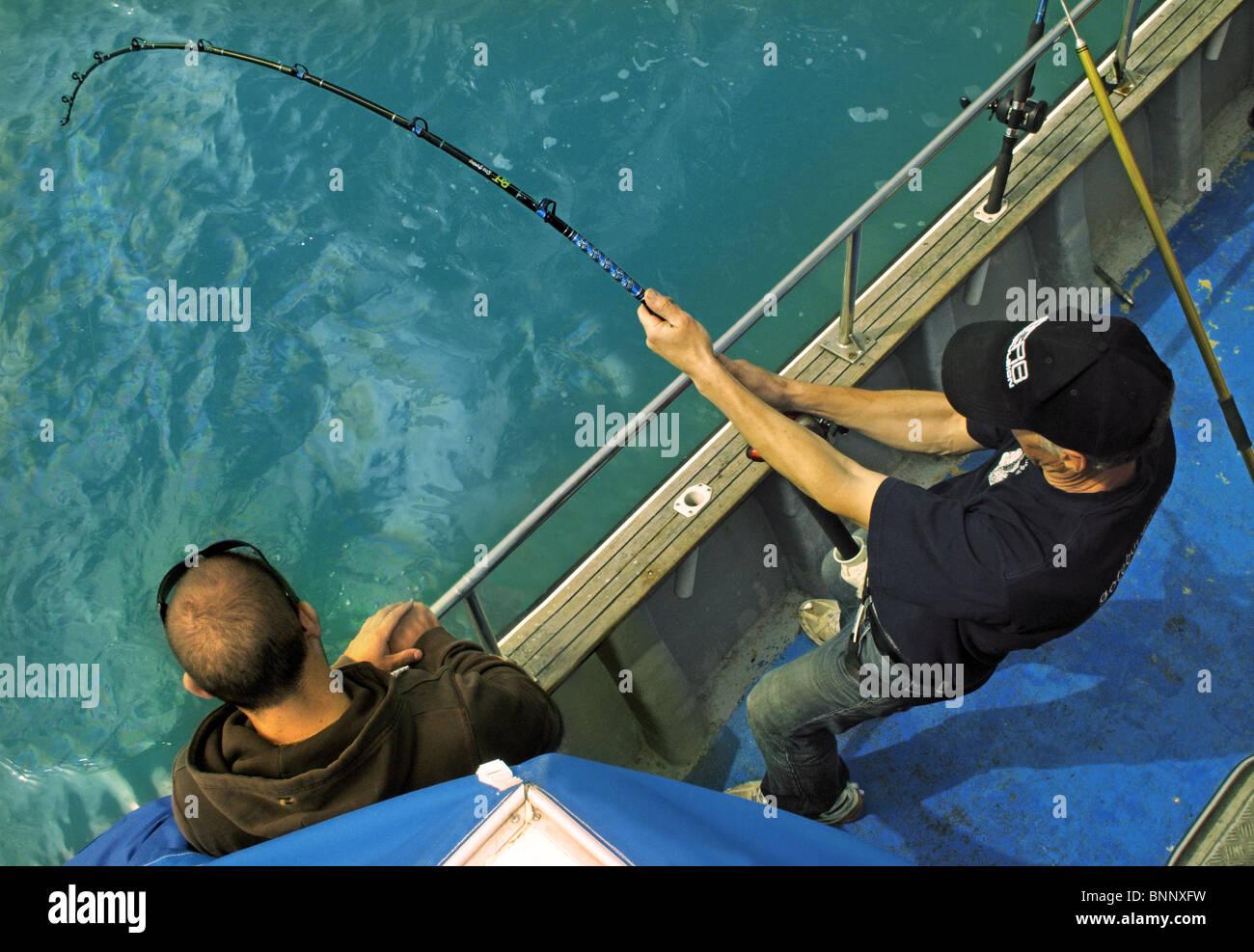 Man deep sea fishing: Big fish on the hook bends the rod. - Stock Image