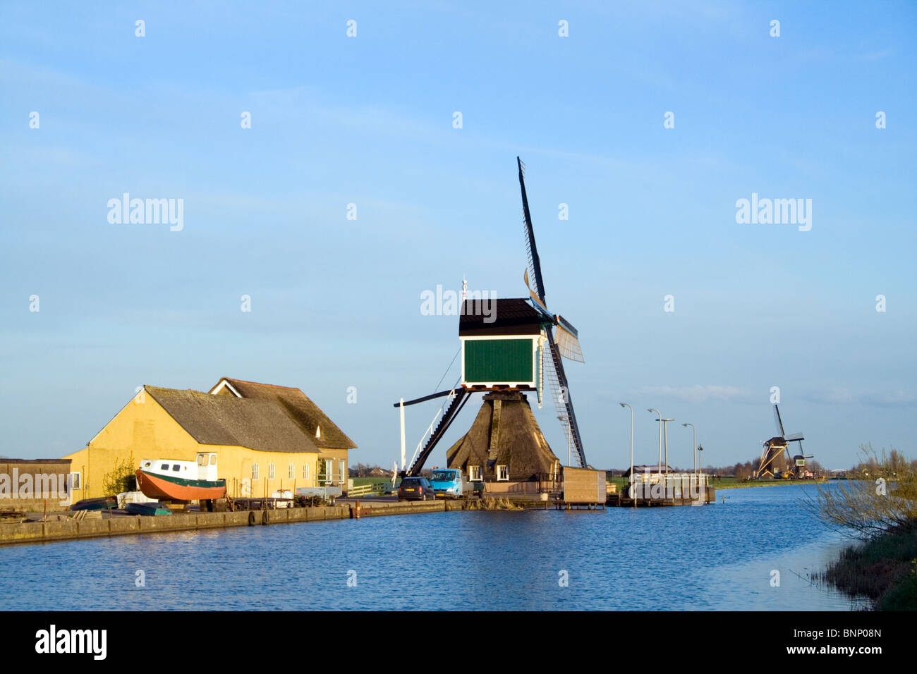 Windmill next to a river in a polder in Holland - Stock Image