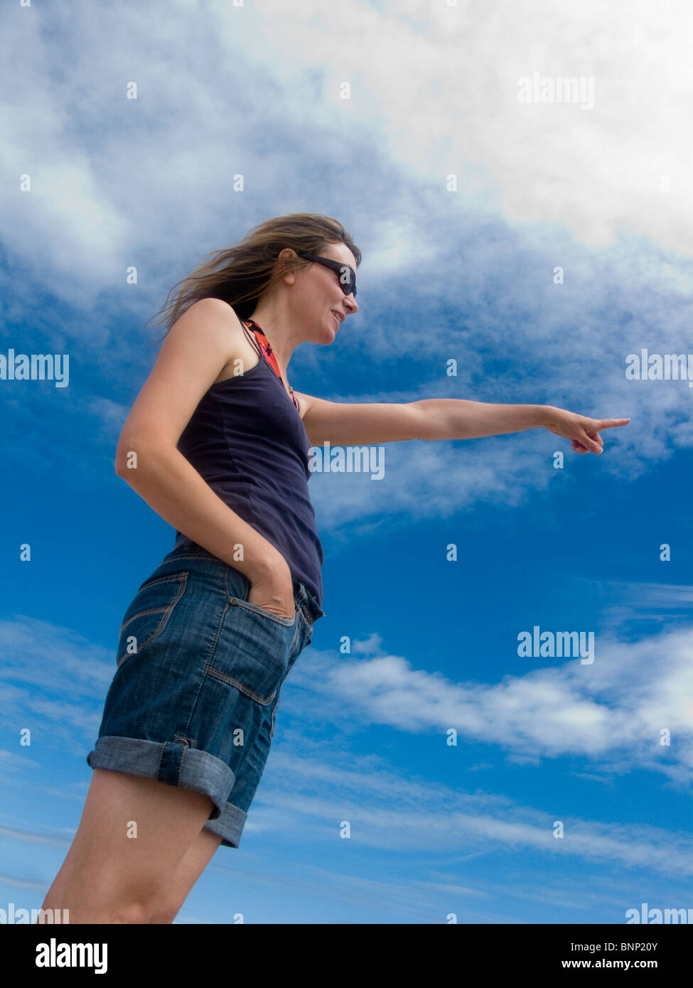 woman pointing, stood against sky - Stock Image