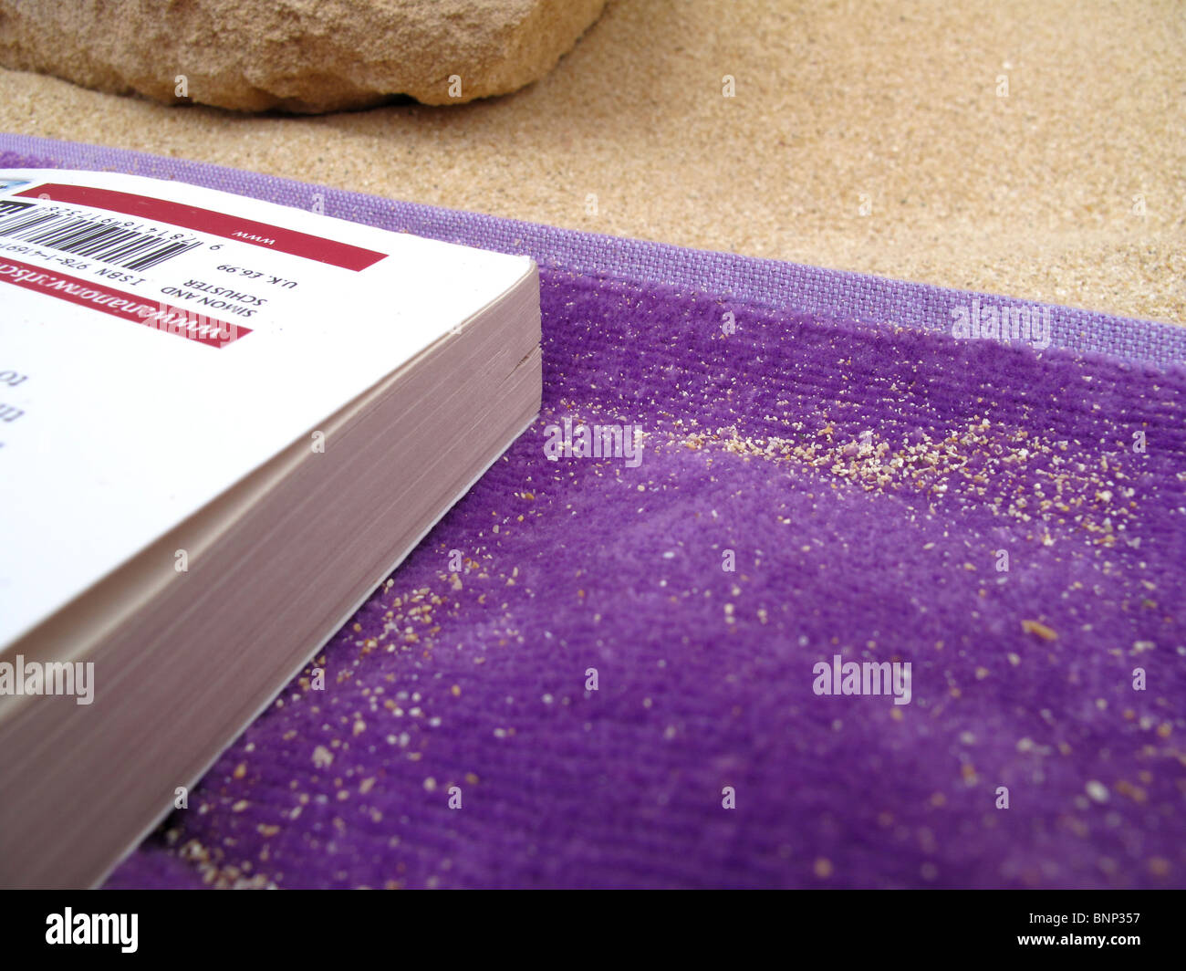 Paperback book on towel on beach - Stock Image