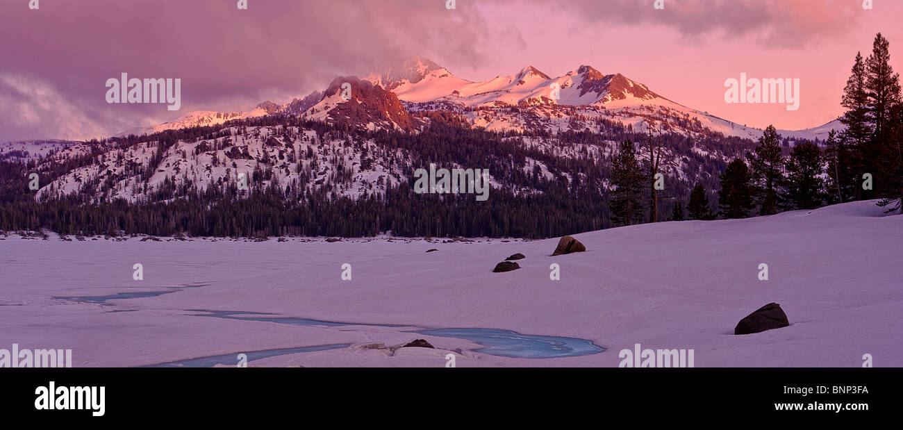 Spring thaw reveals blue ice and sunset light on mountains at Caples Lake, Carson Pass, California, USA. - Stock Image