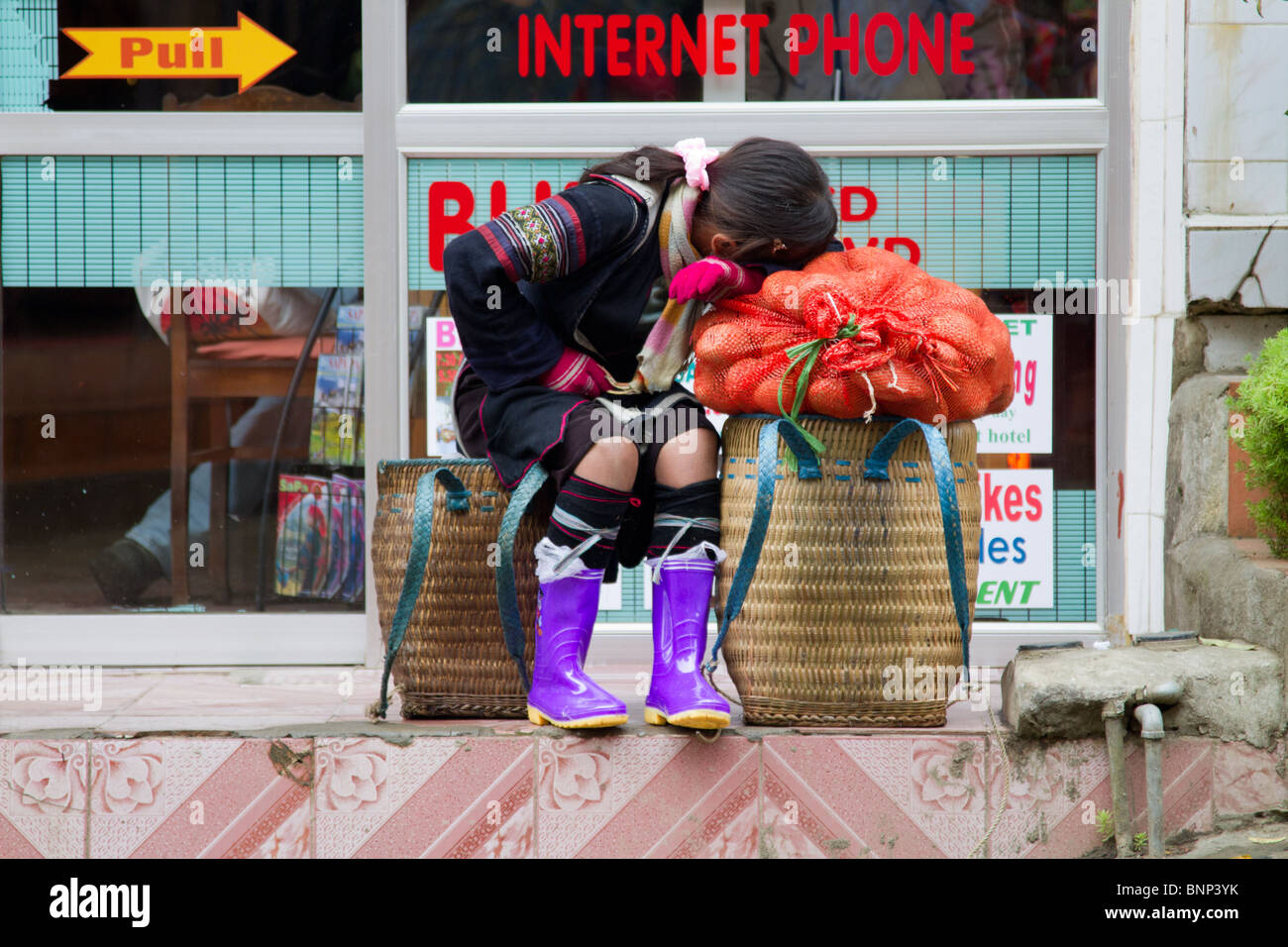A black Hmong girl rests on her purchases in front of an Internet café on the street in Sapa - Stock Image