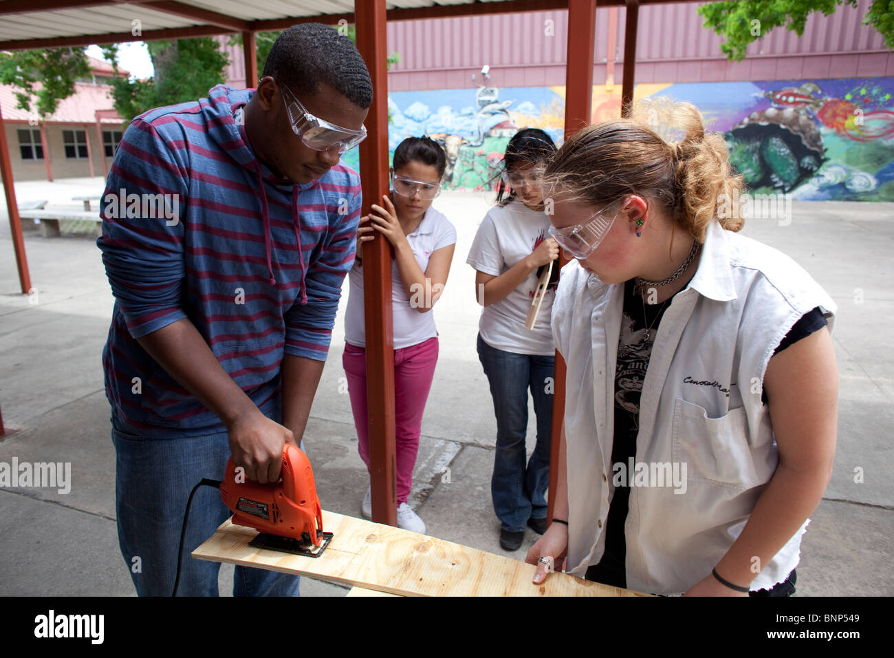 Students in safety goggles watch fellow student use power tool to cut wood for body of model solar car for engineering - Stock Image
