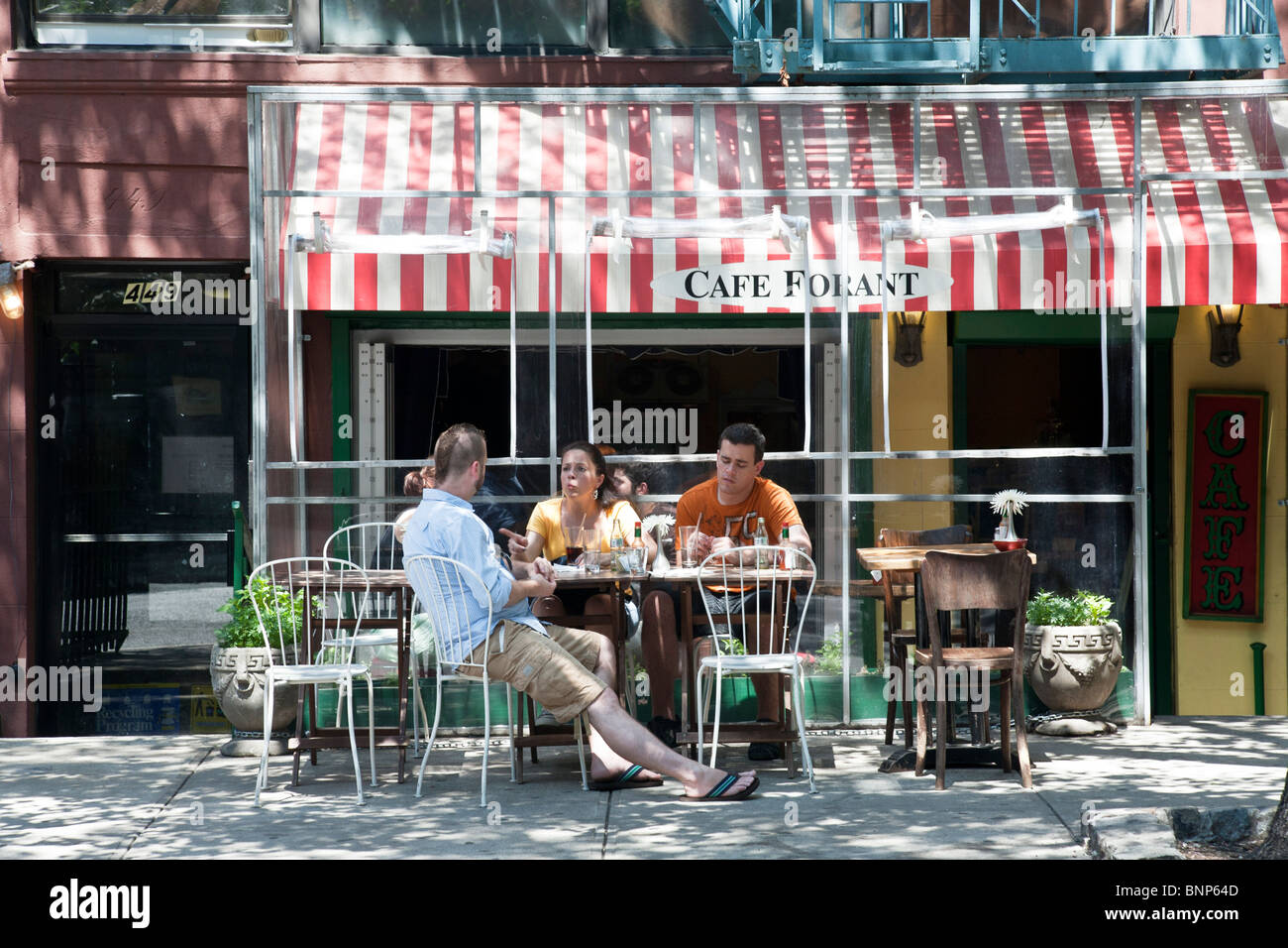 animated young woman with 2 male friends relaxing at tree shaded outdoor tables seating of small charming cafe on - Stock Image