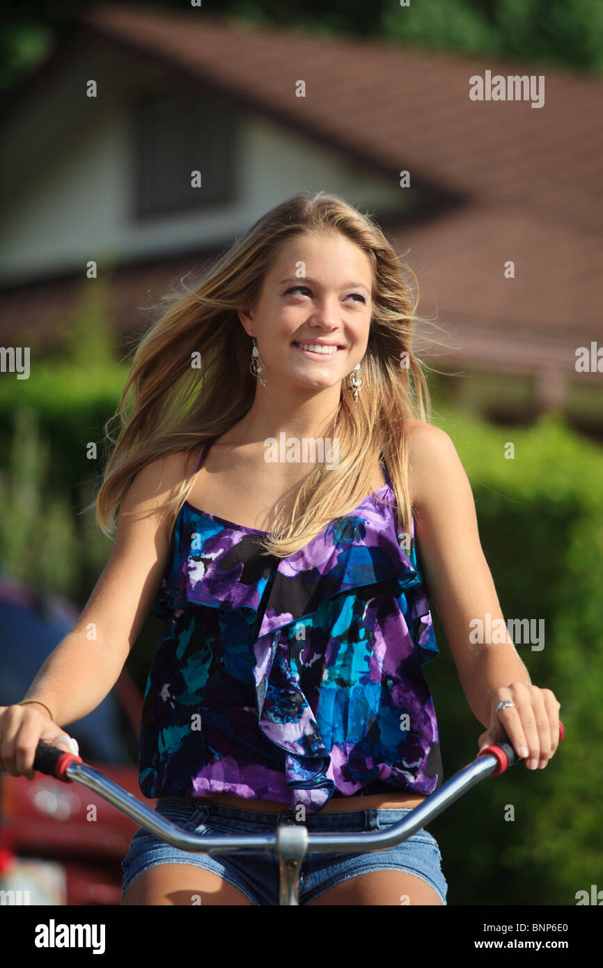 pretty blond,teenage girl rides her bicycle - Stock Image