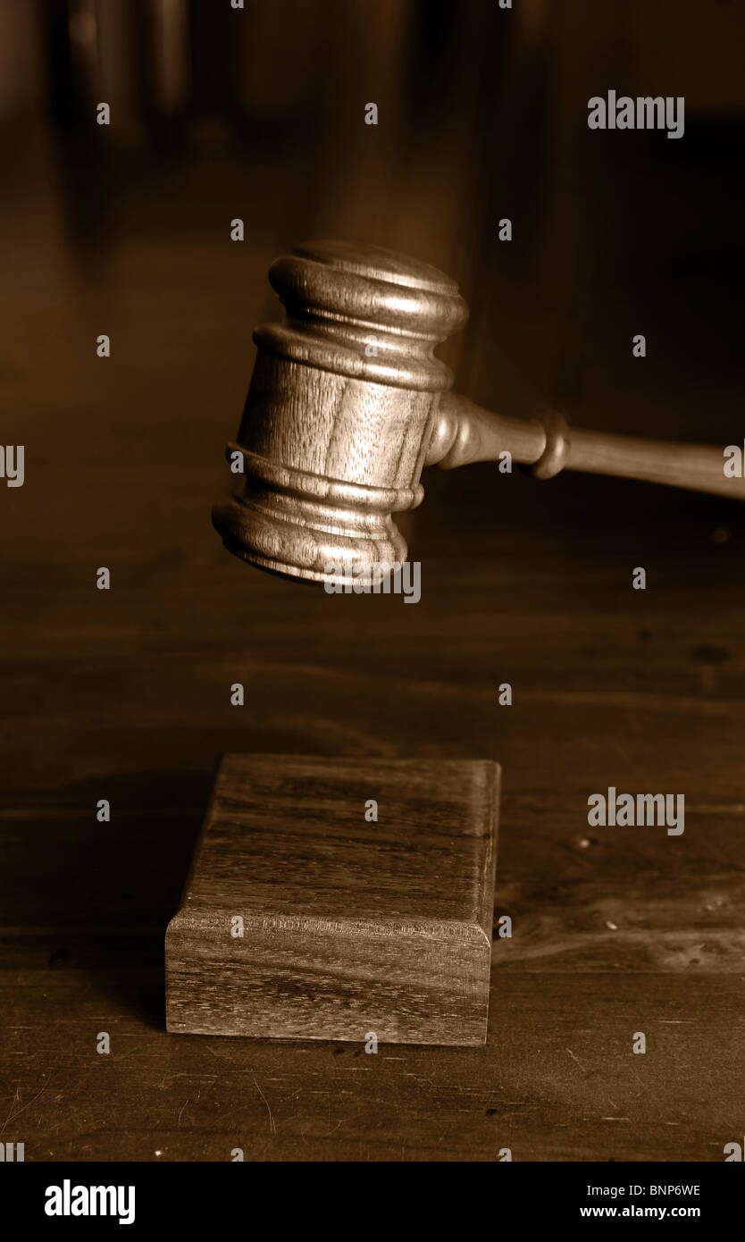 judges gavel coming down and hitting the block gavel blurred for movement - Stock Image