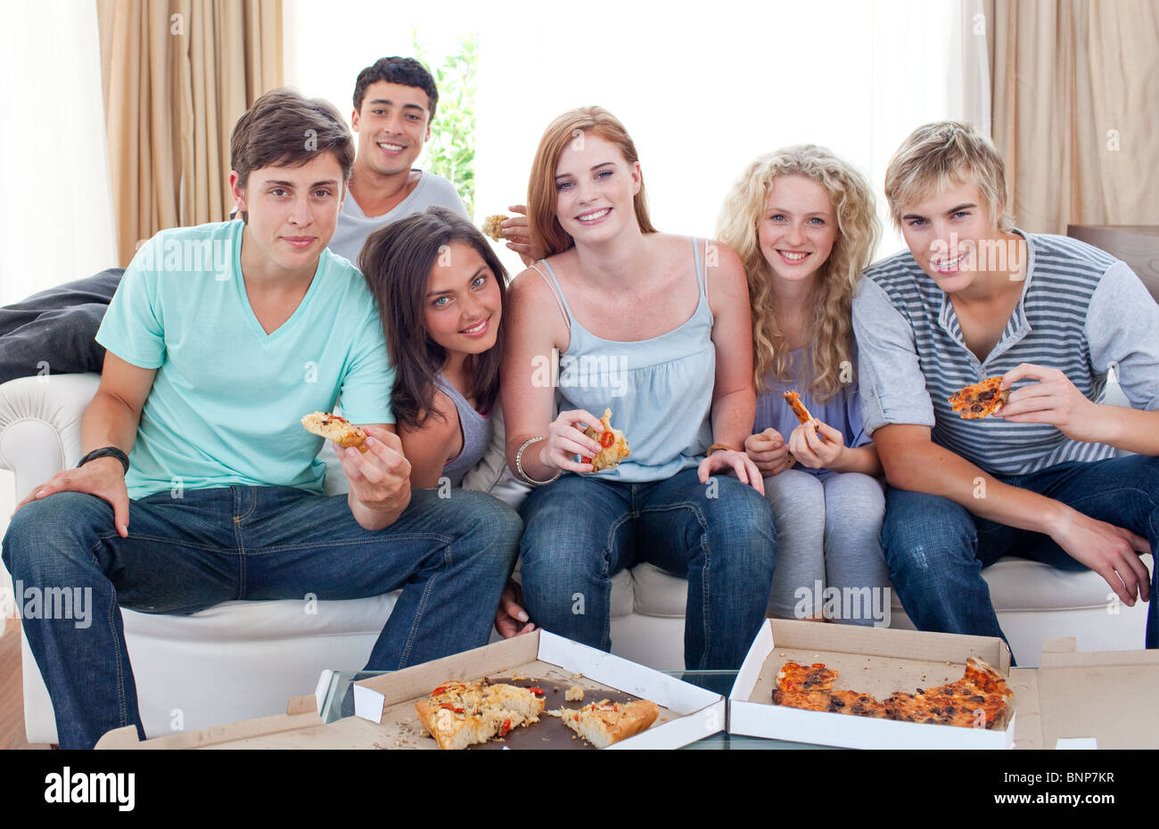 Adolescents eating pizza at home - Stock Image