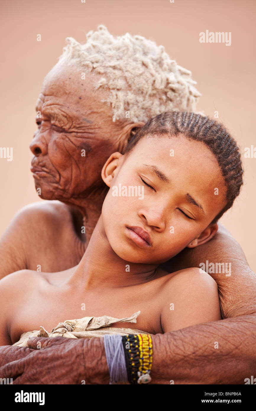 Bushman/San People. Young girl with old woman embracing - Stock Image