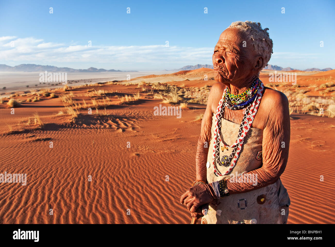 Elderly Bushman / San woman standing in desert - Stock Image