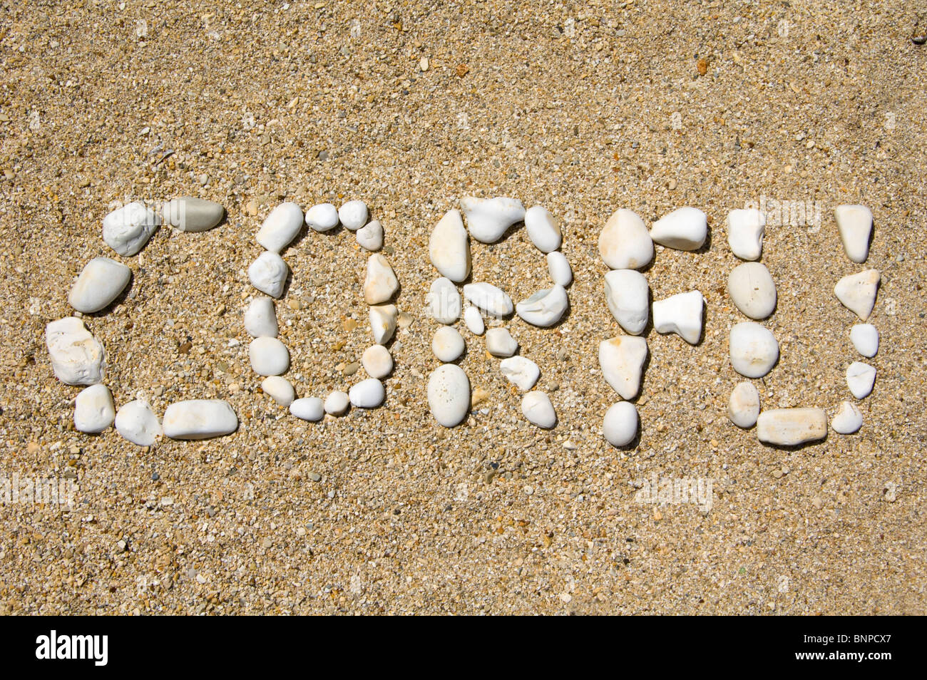 CORFU spelled out in pebbles on a beach at Kassiopi on the Greek Mediterranean island of Corfu Greece GR - Stock Image