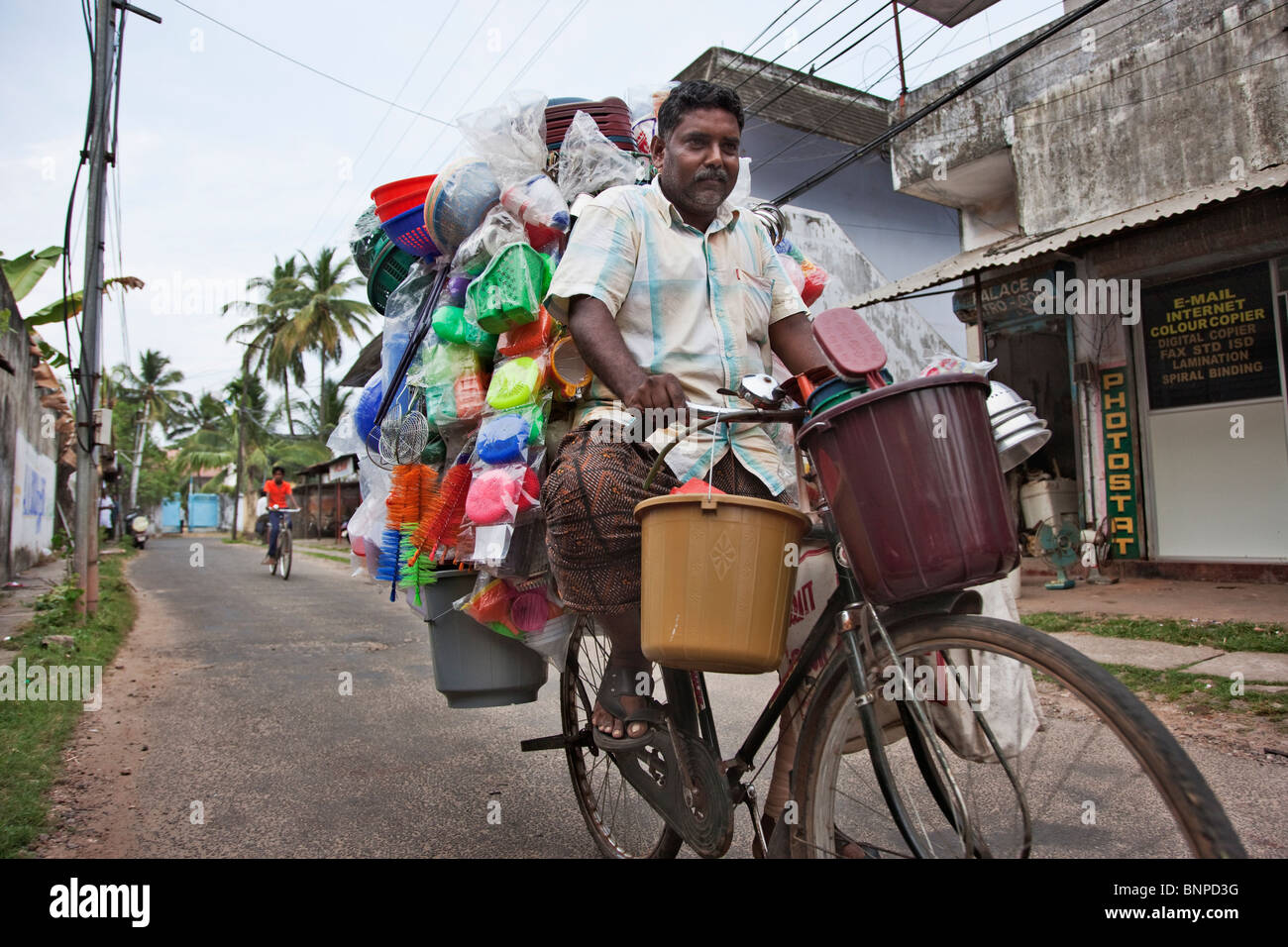 Middle aged Man on bicycle selling various types of plastic household items cycling down a rural city street - Stock Image