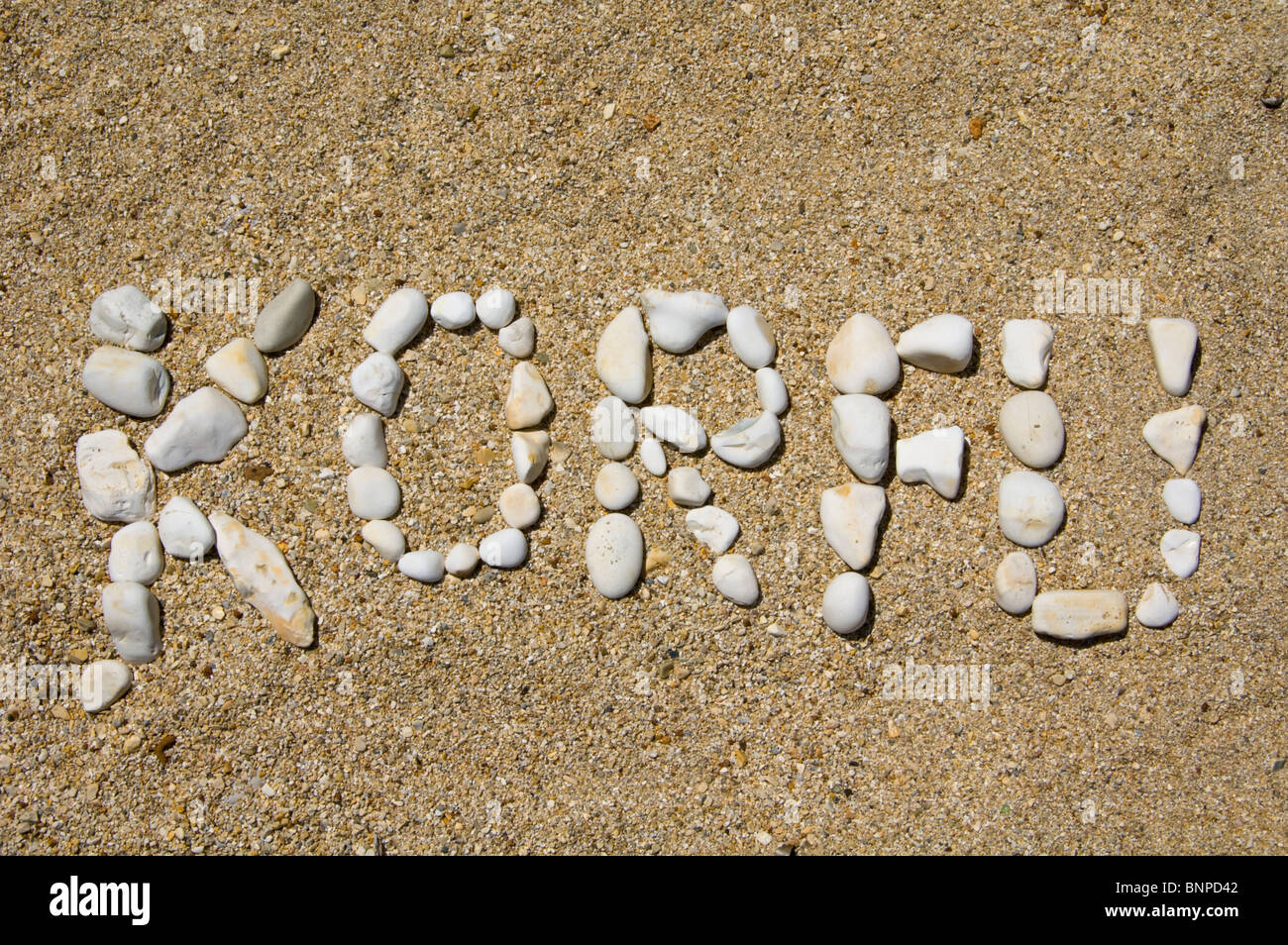 KORFU spelled out in pebbles on a beach at Kassiopi on the Greek Mediterranean island of Corfu Greece GR - Stock Image
