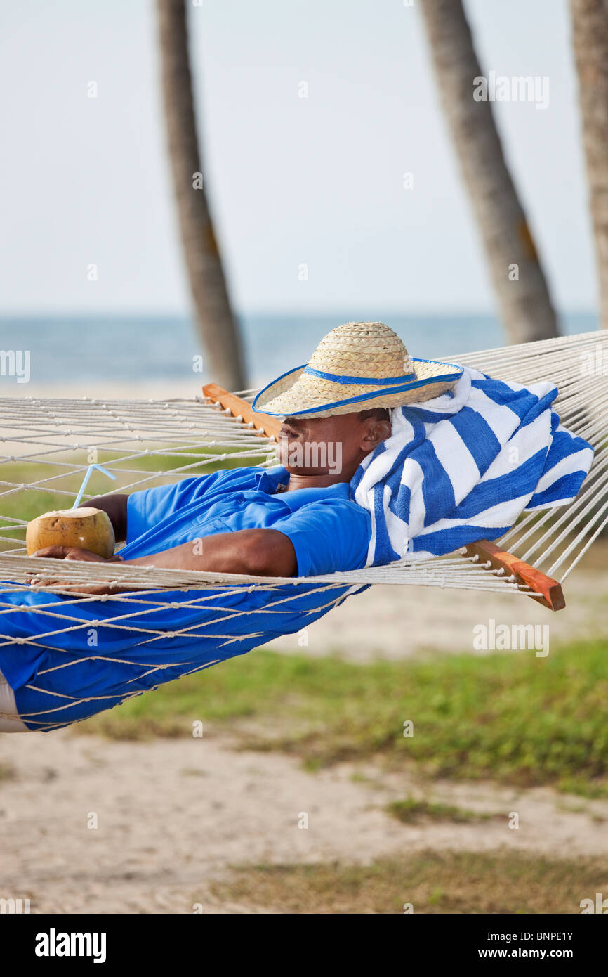 Young indian man relaxing in a hammock Stock Photo