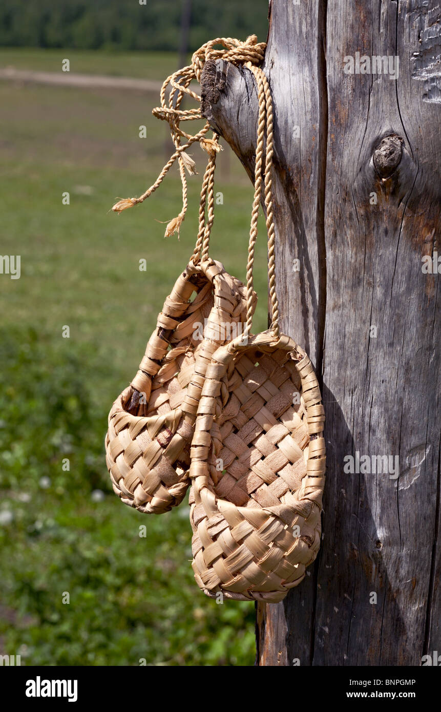 Bast shoes made with old technology hanging on the pole - Stock Image