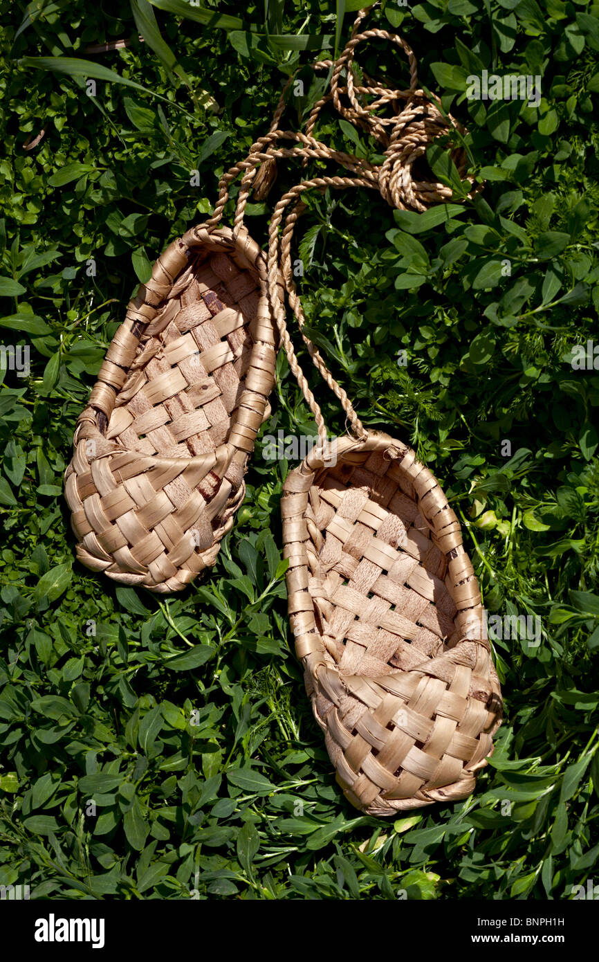 Bast shoes made with old technology on a green grass - Stock Image